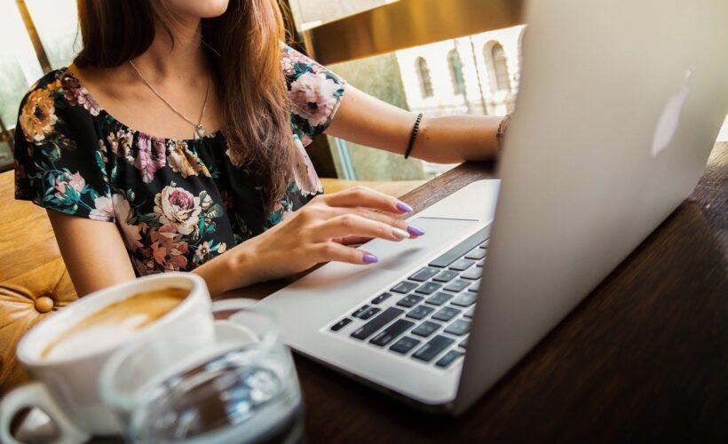 Kvinde bruger computer på altan med kaffe ved siden