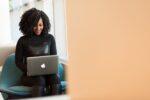 Kvinde er glad imens hun bruger computeren