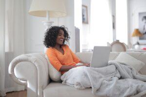 Kvinde griner af noget på computeren