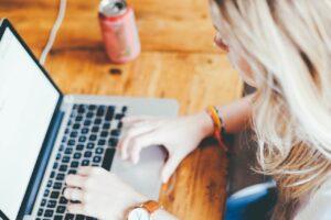 Kvinde sidder og køber ting på nettet ved computer