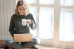 Person drikker kaffe og kigger på sin bærbar