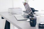 Skrivebord fyldt med kontor artikler og computer
